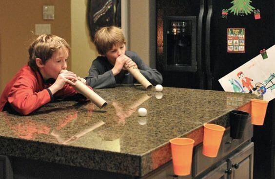 Meninos brincando de acerte o alvo na mesa de jantar