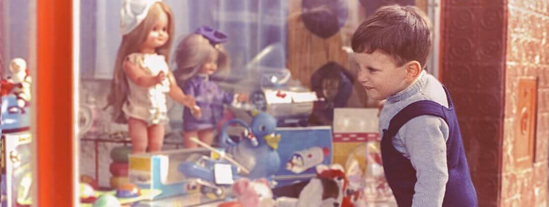 Criança olhando vitrine de loja de brinquedos antigos
