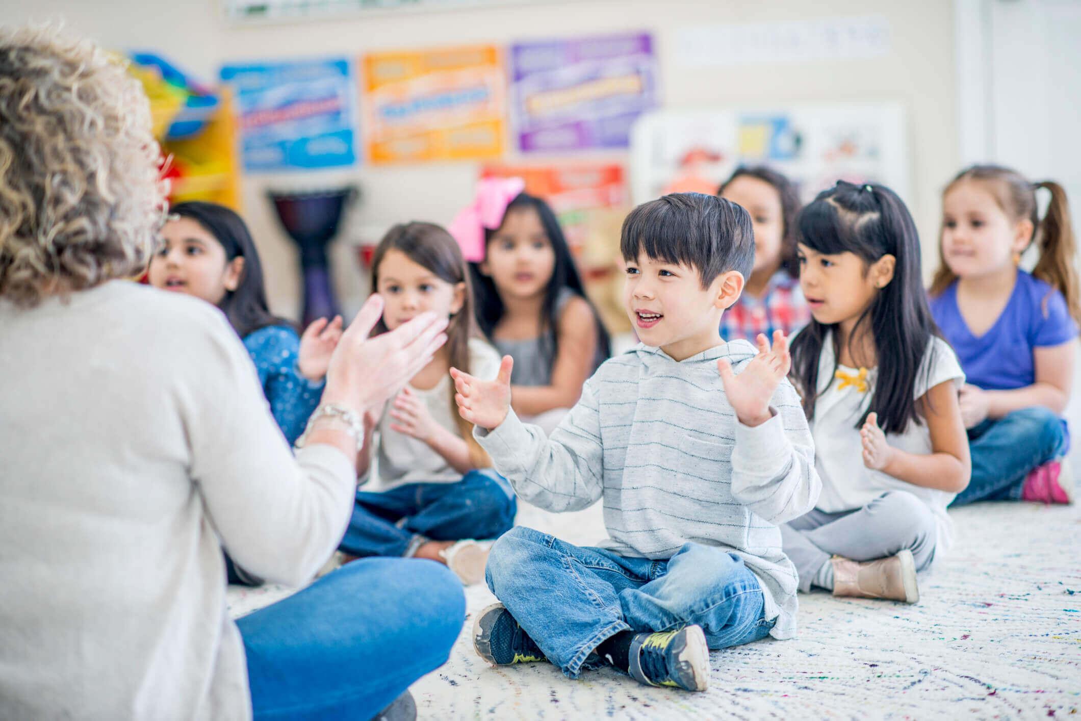 Crianças cantando e batendo palmas com a professora