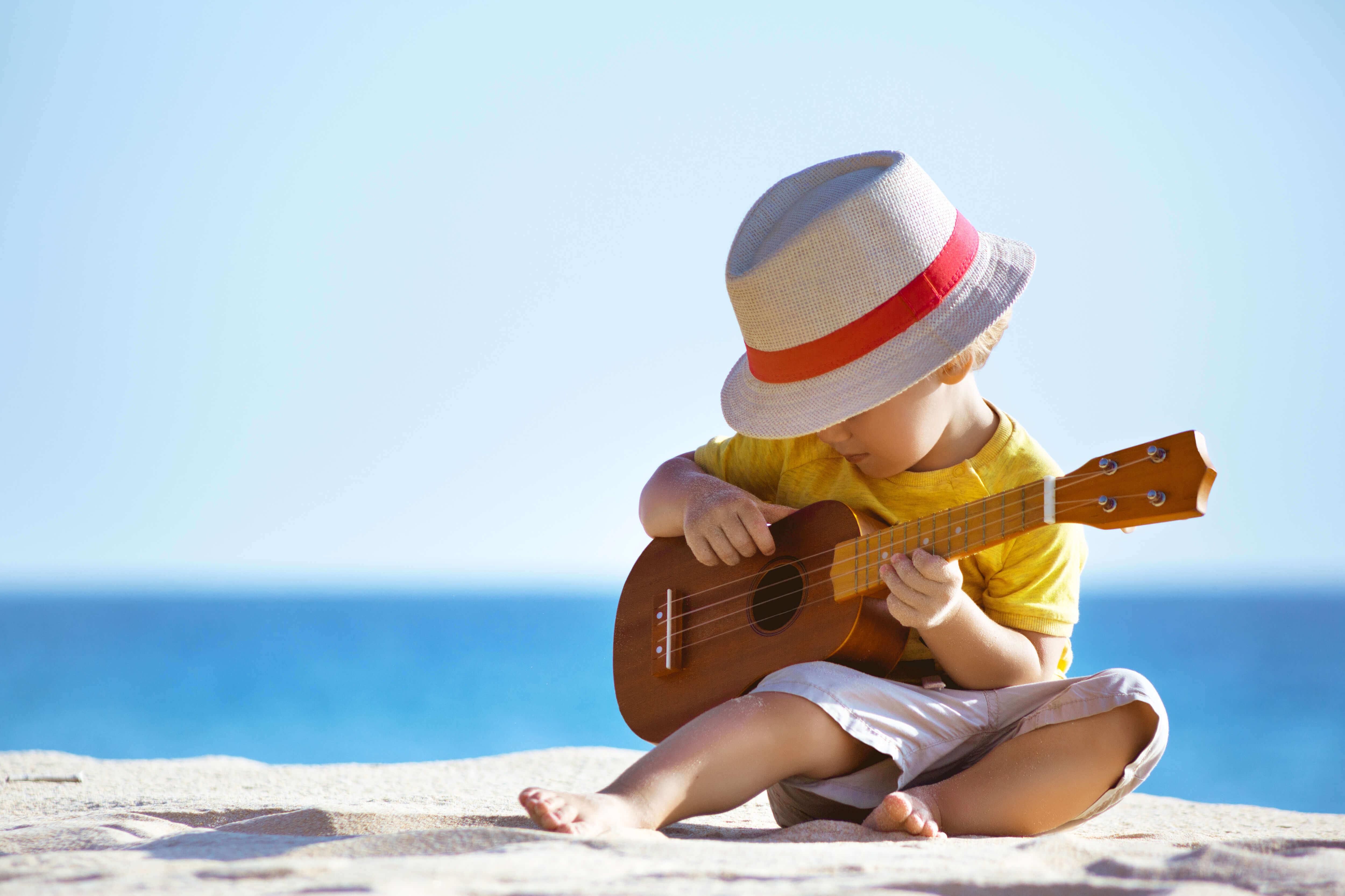 Menino tocando violão na praia