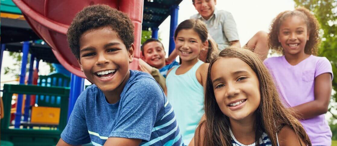 Seis crianças sorrindo e ao fundo um playground