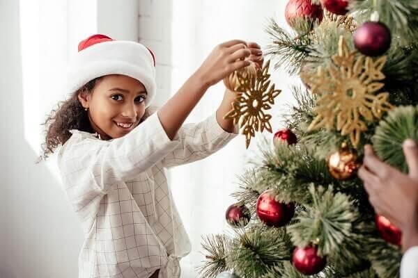 Menina colocando enfeite de natal na árvore de natal