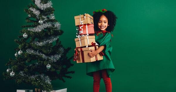Menina segurando presentes de natal ao lado da árvore de natal